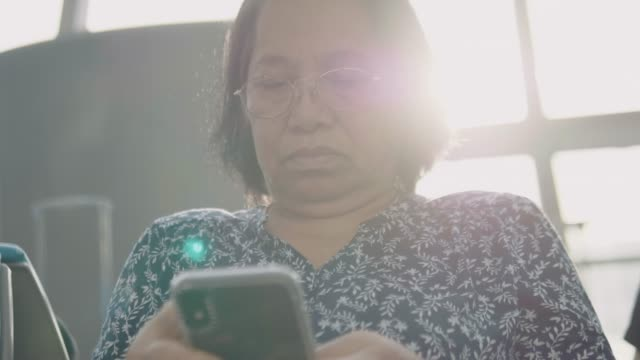 matual woman using smartphone at the airport - the ageing process stock videos & royalty-free footage