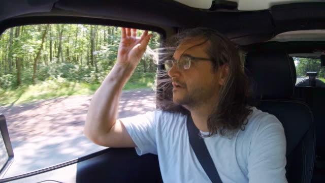 vídeos de stock e filmes b-roll de mature, 45-years-old, long-haired man wearing eyeglasses riding a car as a passenger. the road trip across pennsylvania, usa. - 45 49 years
