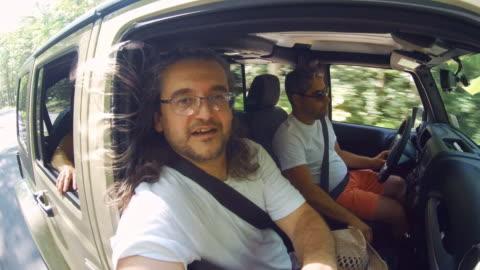 mogen, 45 år gammal, långhårig man bär glasögon ridning en bil som passagerare. roadtrip över pennsylvania, usa. - 45 49 år bildbanksvideor och videomaterial från bakom kulisserna