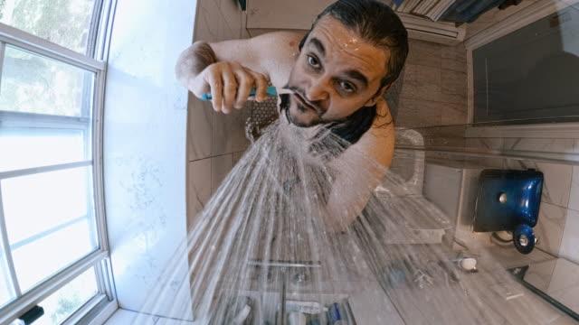 reifen 45 jahre alte mann zähneputzen unter der dusche im heimischen badezimmer. - bürsten stock-videos und b-roll-filmmaterial