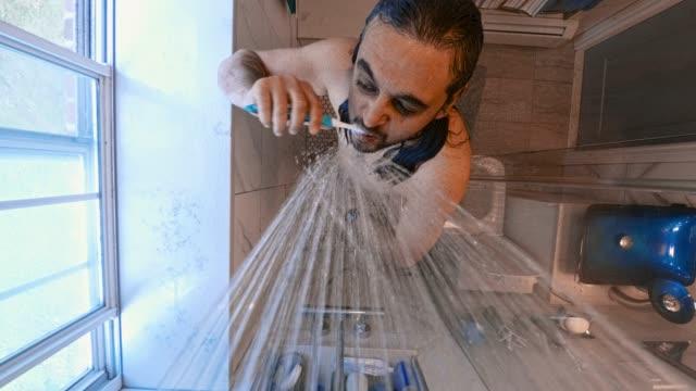 vídeos de stock, filmes e b-roll de homem de 45 anos de idade maduro escovar os dentes debaixo do chuveiro no banheiro interno. - domestic bathroom