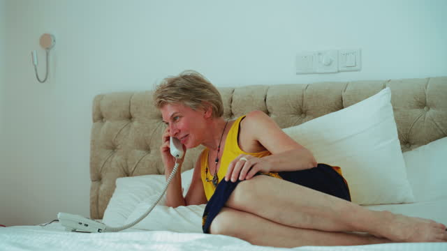 mature 55-years-old woman calling hotel service lying on a bed in a bright and clean modern hotel room. - 55 59 years stock videos & royalty-free footage