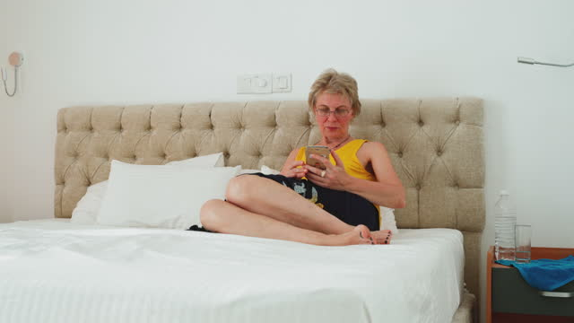 mature 55-years-old woman texting with a smartphone when she sitting on a bed in a bright and clean modern hotel room. - 55 59 years stock videos & royalty-free footage