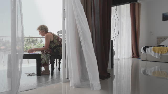 mature 55-years-old woman working on a balcony in a contemporary hotel in bentota, sri lanka. - 55 59 years stock videos & royalty-free footage