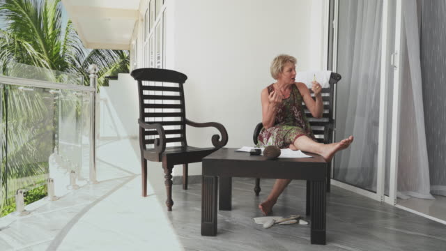 mature 55-years-old woman working on an open-air balcony in a contemporary hotel, talking with someone who is hidden in a room. - 55 59 years stock videos & royalty-free footage
