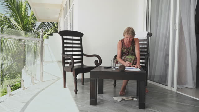 mature 55-years-old woman working on an open-air balcony in a contemporary hotel - 55 59 years stock videos & royalty-free footage
