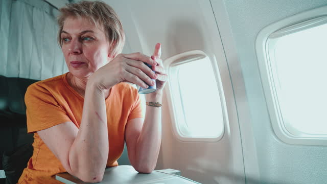 mature 55-years-old women drinking a tea in the flight, aboard of airplane. - 55 59 years stock videos & royalty-free footage