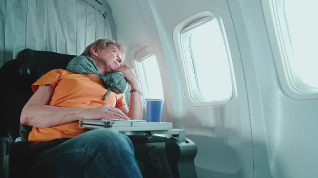 mature 55-years-old women looking into the window during a flight aboard of airplane. - 55 59 years stock videos & royalty-free footage
