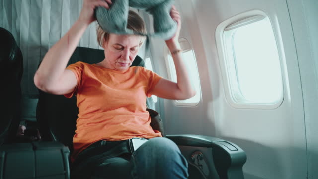mature 55-years-old women preparing to rest, comforting herself with a travel pillow during the flight, aboard of airplane. - 55 59 years stock videos & royalty-free footage