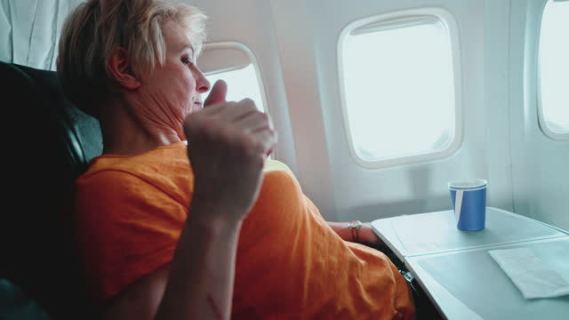 mature 55-years-old women resting during the flight, aboard of airplane. - 55 59 years stock videos & royalty-free footage