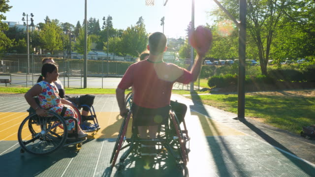 ms mature adaptive athlete passing basketball to teammate during practice on outdoor court - disability stock-videos und b-roll-filmmaterial