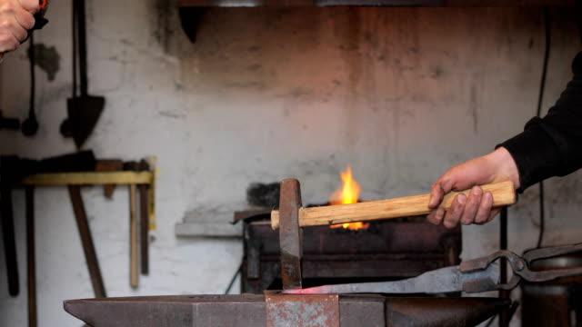 成熟した大人と若い大人鍛冶ハンマーがアンビルに鉄を加熱 - ワーキングシニア点の映像素材/bロール