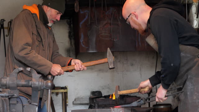 Mature Adult And Young Adult Blacksmith Hammering Heated Iron on Anvil