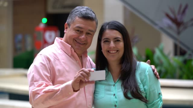 vidéos et rushes de couples adultes matures au centre commercial faisant face à la caméra souriant tout en montrant une carte pour éditer - carte de fidélité