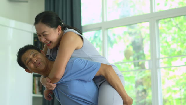mature adult couple have a piggy back ride in living room. - solo adulti video stock e b–roll