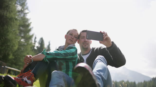 Mature Adult Couple taking picture on holiday with smart phone
