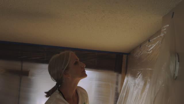 maturo adulto adulto femmina fai-da-casa ristrutturare dipingere pareti soffitti e porte serie video - bricolage video stock e b–roll
