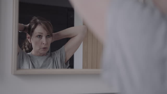 vídeos de stock e filmes b-roll de mature adult female doing up hair in bathroom and looking in mirror - um dia na vida de