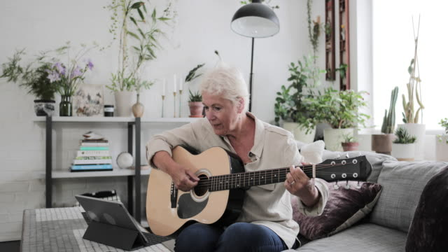 vídeos de stock, filmes e b-roll de mature adult female learning to play the guitar at home with a video tutorial - tutorial