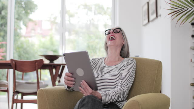 mature adult female on a videocall to family - baby boomer stock videos & royalty-free footage