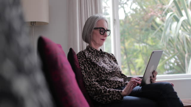 mature adult female using a digital tablet - lesebrille stock-videos und b-roll-filmmaterial