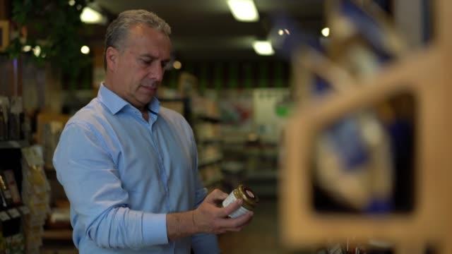 vídeos de stock, filmes e b-roll de adulta madura, compras em um mercado gourmet, escolhendo diferentes marmeladas adicioná-los ao cesto - geleia