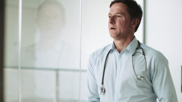 Mature Adult Male Doctor in Hospital looking out of window