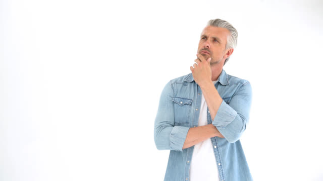 Mature adult man standing thinking very serious and thoughtful