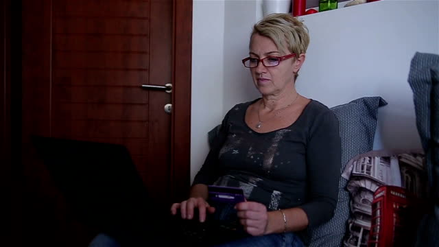 Mature adult woman buying online with credit card
