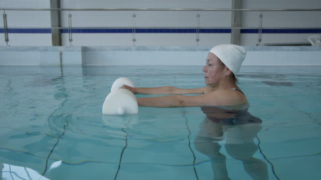 mature adult woman exercising her legs and arms during hydrotherapy at a rehab clinic - hydrotherapy stock videos & royalty-free footage