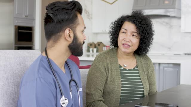 stockvideo's en b-roll-footage met volwassen volwassen vrouw ontmoeting met mannelijke arts - huisbezoek