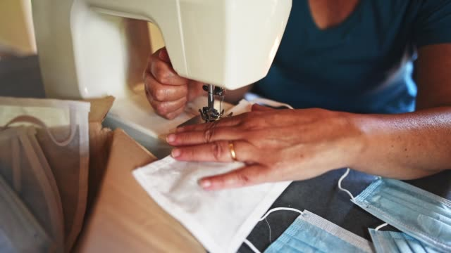 mature adult woman sewing face mask for covid at home - sewing machine stock videos & royalty-free footage