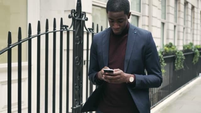 stockvideo's en b-roll-footage met volwassen afro-amerikaanse zakenman met behulp van telefoon terwijl het gaan werken - blazer