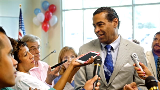 Mature African American politician answers questions after political rally