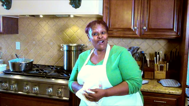 Mature African American woman in kitchen drying hands
