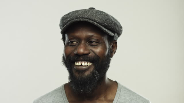 Mature african man laughing and looking away on gray background