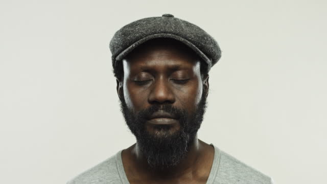mature african man with flat cap in studio - eyes closed stock videos & royalty-free footage