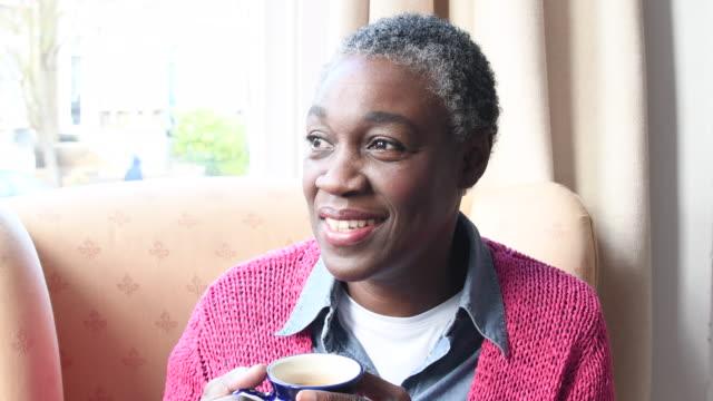 Reife afrikanische Frau sitzen und entspannen Sie bei einer Tasse Tee