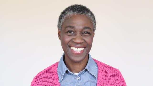vídeos y material grabado en eventos de stock de mujer africana madura sonriendo y volviendo a la cámara de la cara - cabello corto