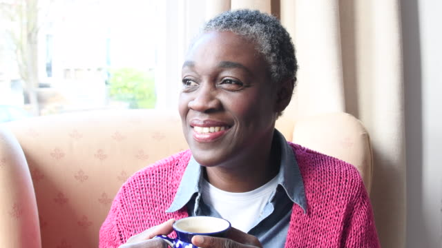 Mature African woman with hot drink smiling and turning to face camera