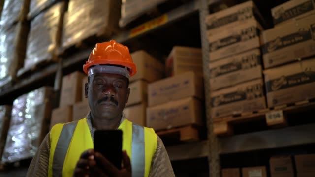 vídeos de stock, filmes e b-roll de trabalhador africano maduro que usa o telefone móvel no armazém - capacete de trabalho