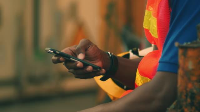 vídeos y material grabado en eventos de stock de trabajador africano maduro usando el teléfono móvil en el almacén - trabajador de línea de montaje