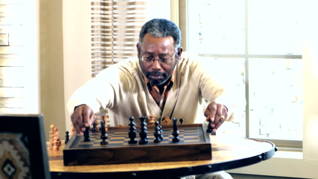 Mature African-American man setting up chess board