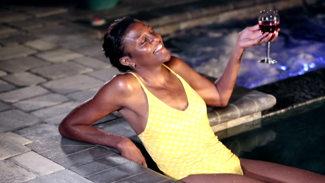 vídeos de stock e filmes b-roll de mature african-american woman in pool relaxing at night - swimwear