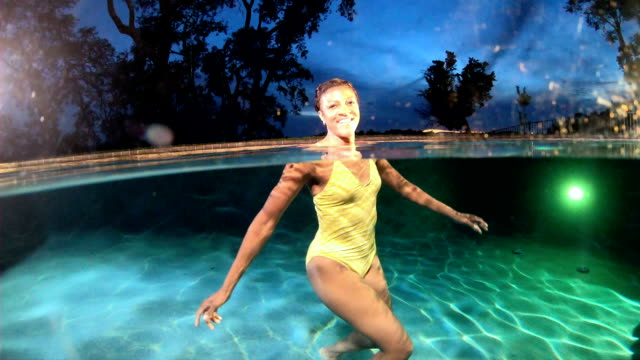 Mature African-American woman in pool relaxing at night