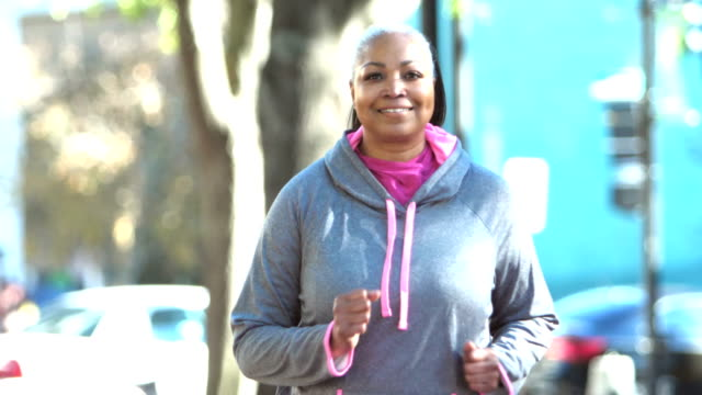 mature african-american woman power walking in city - sportswear stock videos & royalty-free footage
