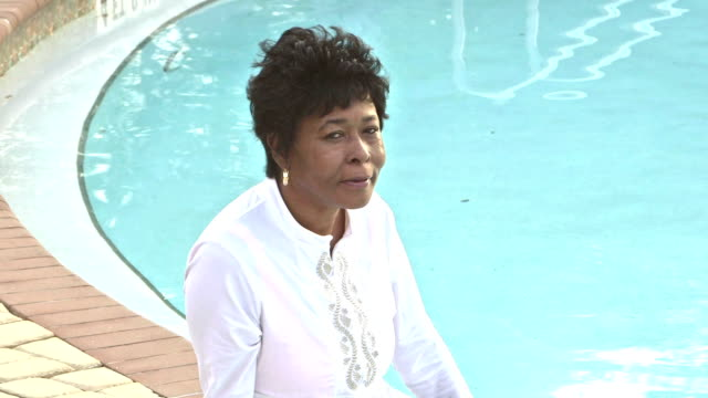 Mature African-American woman sitting poolside