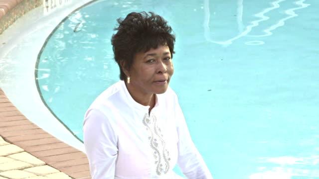 reife afro-amerikanische frau sitzen am pool - 55 59 jahre stock-videos und b-roll-filmmaterial