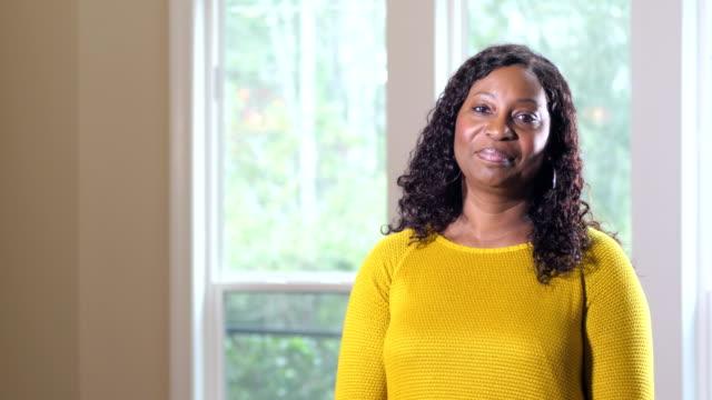 vidéos et rushes de femme mature d'afro-américain restant par la fenêtre - adulte d'âge mûr