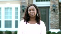 Mature African-American woman standing in front of house